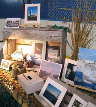 Shoreline creations has used materials that go well with their images of fishing communities – fishing nets, floats and weathered crates make the props and table covering for their work. Photo: J. Pye
